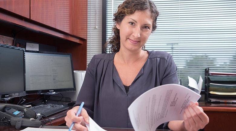Attorney Cara Kirkpatrick working in her office at The Sam Bernstein Law Firm in Farmington Hills, Michigan