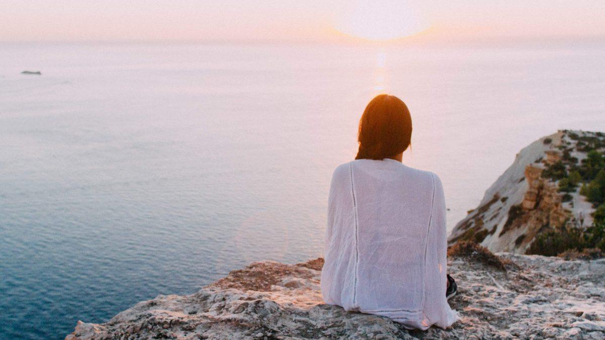 woman looking at water at dawn