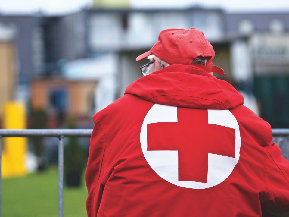 man with red cross jacket